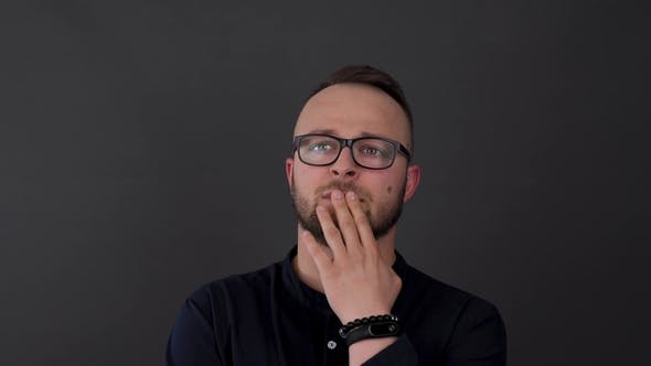 Thumbnail for A Young, Bearded Man with Glasses. Studio Shot of Male Thinking About Something, Then Waving with