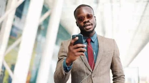 Thumbnail for African American Businessman in the Sunglasses Talking on the Phone with Headphones Near the Office