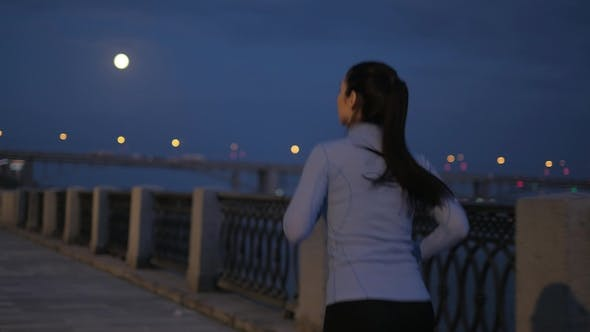 Thumbnail for Night Jogging. a Girl in Sports Clothes Runs Along a Deserted Night Embankment in the Background of