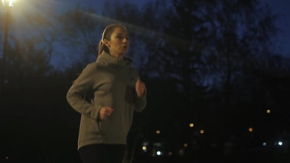 Thumbnail for Evening Jog Girl Runs Along the Embankment on the Background of the Night City