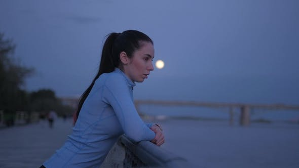 Thumbnail for Girl in Sports Clothes Is Resting Her Elbows on the Fence on the Embankment