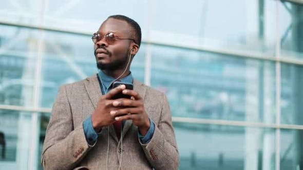 Thumbnail for Portrait of African American Businessman Uses a Smartphone and Listens To Music on Headphones