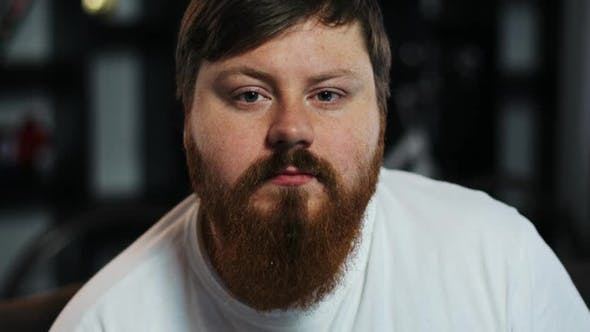 Thumbnail for Fat Man with Read Beard Looks Straight Into the Camera