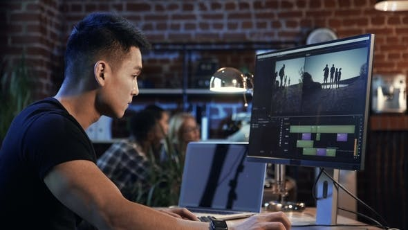 Thumbnail for Ethnic Man Editing Video on Computer