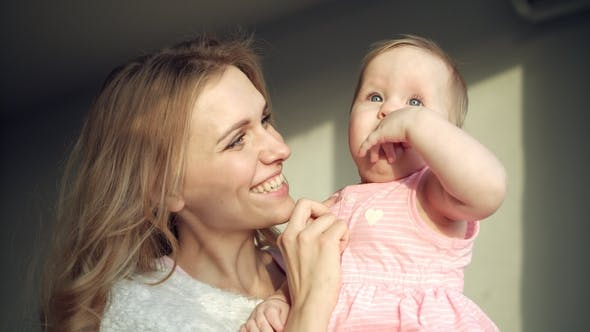 Thumbnail for Happy Mother Holding Baby Girl on Hands. Cheerful Mom Embrace Toddler Girl