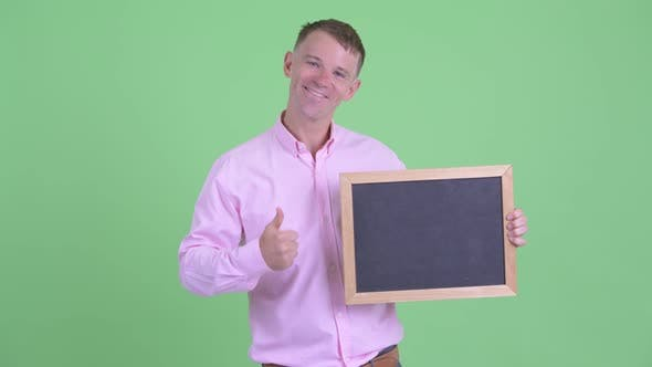 Thumbnail for Portrait of Happy Businessman Holding Blackboard and Giving Thumbs Up