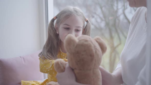 Thumbnail for Portrait of Cute Little Girl Playing with Teddy Bear and Talking with Unrecognizable Grandmother