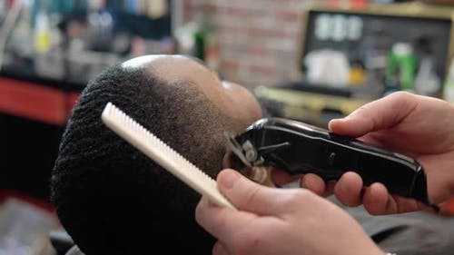 Hairdresser Makes for the Client a Haircut with a Clipper