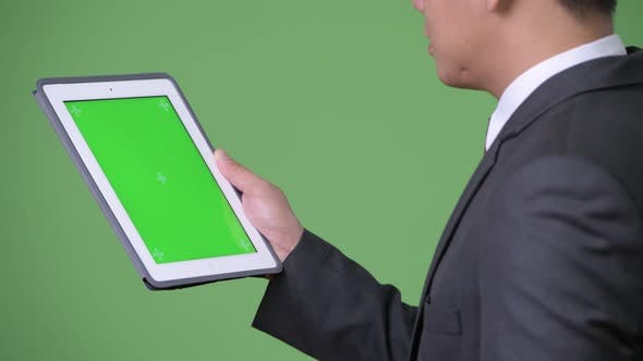 Thumbnail for Young Handsome Asian Businessman Using Digital Tablet