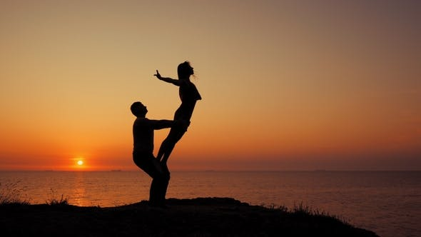 Thumbnail for Amazing Silhouettes of Beautiful Couple Doing Acrobatic Yoga on the Sea or Ocean Beach at Sunrise