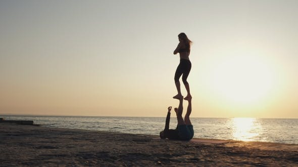 Thumbnail for Silhouettes of Fit Young Couple Doing Acro-yoga at Sea Beach. Man Lying on Concrete Plates and