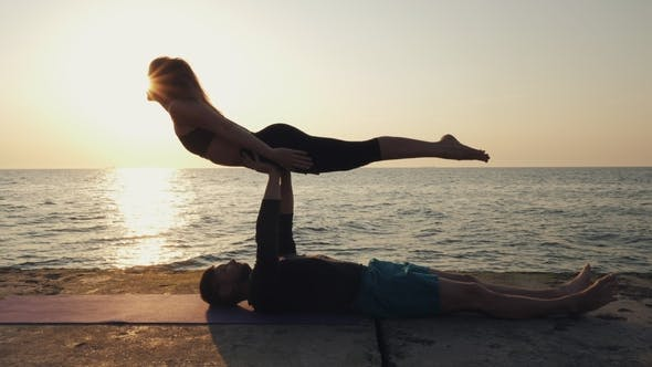 Thumbnail for Silhouettes of Fit Young Couple Doing Acrobatic Yoga at Sea Beach