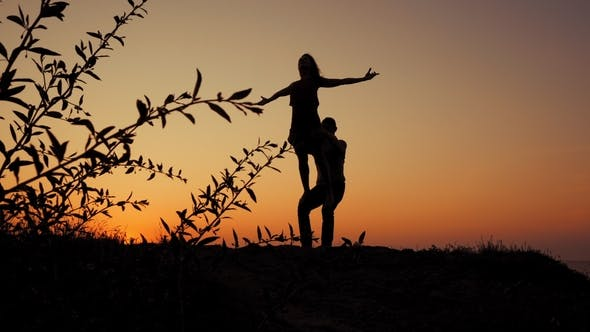 Thumbnail for Beautiful Silhouettes of Beautiful Couple Practicing in Acrobatic Yoga on the Sea
