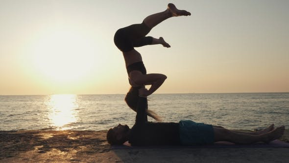 Cover Image for Silhouettes of Fit Young Couple Doing Acro-yoga at Sea Beach
