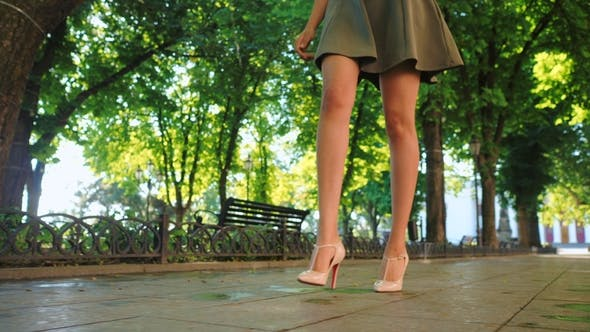Sexy Legs with High Beige Heels Walking in Park of City. Woman Walking on Boulvard Alone. Attractive