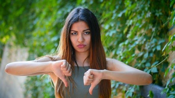 Thumbnail for Junge schöne Frau stehend auf grünem Laub Hintergrund Ausdruck Unzufriedenheit und zeigt Daumen