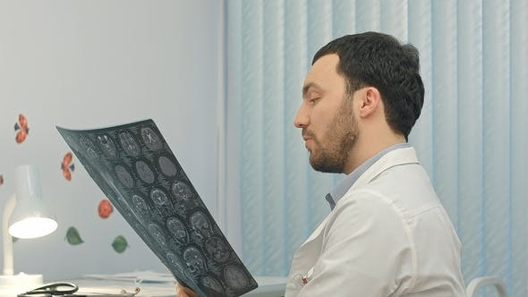 Thumbnail for Concentrated Male Doctor Looking at X-ray Picture in the Medical Office