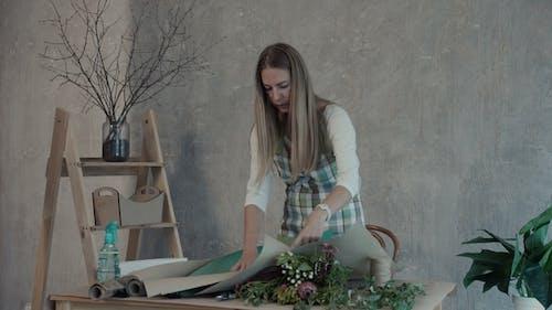 Female Florist Prepares Paper for Packaging Flowers