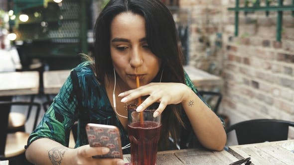 Young Woman Sipping a Cold Drink