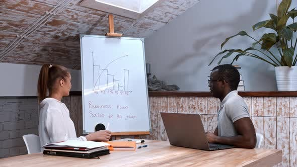 Thumbnail for African-american Man and Caucasian Woman at the Business Meeting - Pointing at the Board with
