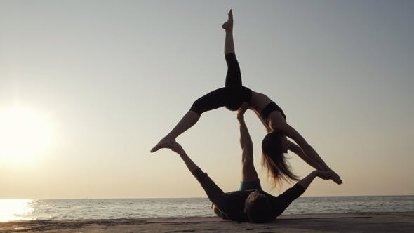 Thumbnail for Silhouettes of Fit Young Couple Doing Acrobatic Yoga at Beach