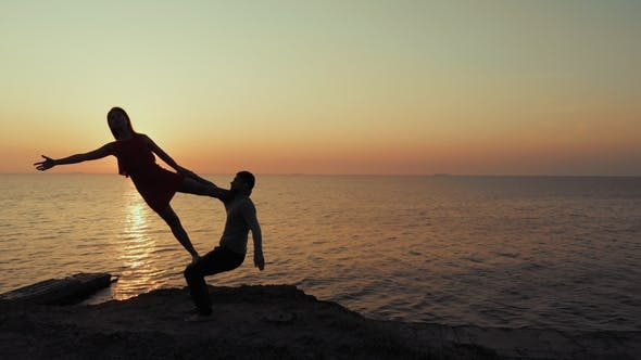 Thumbnail for Silhouette of Young Woman and Man Doing Pair Yoga on Sea Beach at Sunset. Meditation Couple
