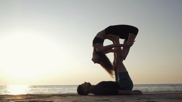 Thumbnail for Silhouettes of Fit Young Couple Doing Acro-yoga at Sea Beach