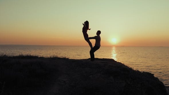 Thumbnail for Silhouette of Young Woman and Man Doing Pair Yoga on Sea Beach at Sunset. Meditation