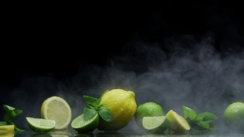 Tropical Lemon and Lime Cuts in Cold Ice Clouds of Fog Smoke on Black Background