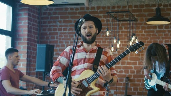 Thumbnail for Emotional Bearded Guitarist Singing Into Microphone