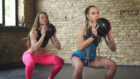 Thumbnail for Sportswomen Doing Squats with Medicine Balls at the Gym