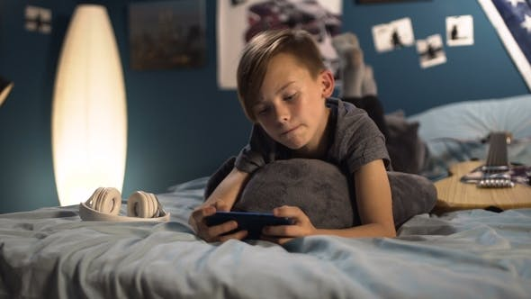 Thumbnail for Boy Playing Smartphone on Bed