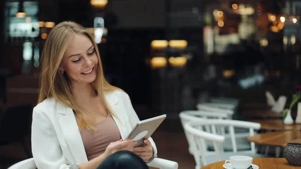 Thumbnail for Smiling Woman Fixes Her Hair Sitting in a Shopping Mall and Reading a Tablet