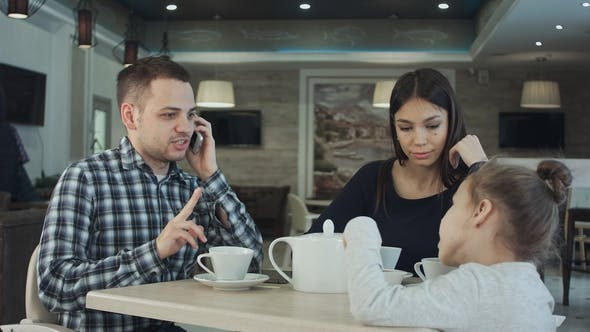 Thumbnail for Mother Trying To Attract Father's Attention To Daughter While He Is Busy Talking To Phone. Mother