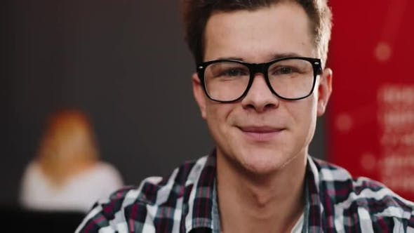 Thumbnail for Smiling Young Man in the Glasses Looks Straight in the Camera