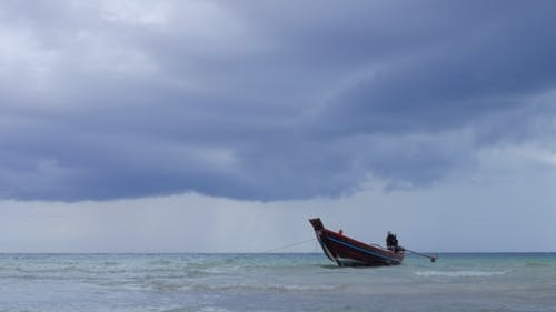 Long Tail Boats Wiggle Near the Beach in Shallow Ocean Water. Storm Clouds in Background, Thailand