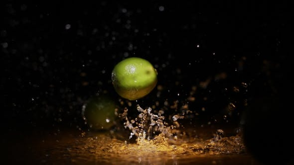Thumbnail for Citrus Limes Falling on Wet Surface in Orange Light Spot and Black Background