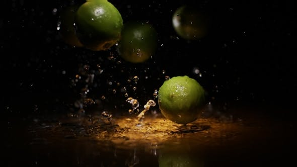 Thumbnail for Citrus Fruits Lime Falling on Water Surface with Splashes and Drops of Water in Orange Light Spot