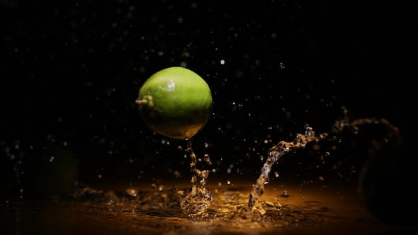 Thumbnail for Citrus Limes Falling in Water in Orange Light Spot with Droplets and Splashes