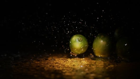 Cover Image for Fresh Limes Falling on Water Surface in Light Spot with Liquid Splash and Droplets in