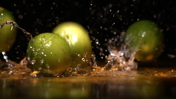 Cover Image for Lime Fruits Falling on Water Surface in Orange Light Spot and Cloud of Fog Splash and Drops