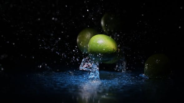 Cover Image for Limes Falling on Water Surface in Blue Light Spot with Liquid Splash and Drops