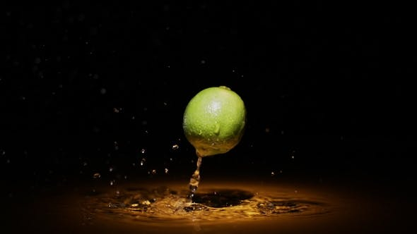 Thumbnail for Green Citrus Lime Falling in Water in Orange Light Spot with Droplets and Splashes