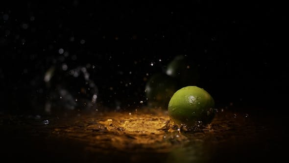 Cover Image for Citrus Fruits Limes Falling on Water Surface in Light Spot with Liquid Splash and Droplets