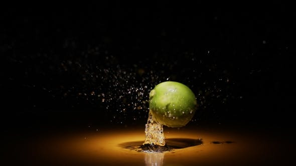 Thumbnail for Citrus Fruit Lime Falling in Water in Orange Light Spot with Droplets and Splashes
