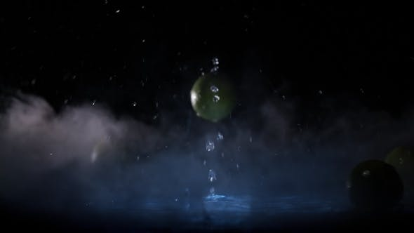 Cover Image for Lime Fruits Falling on Water Surface in Blue Light Spot and Cold Fog Cloud