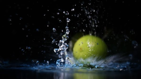 Cover Image for of Lime Fruits Falling on Water Surface in Blue Light Spot with Liquid Splash and Drops
