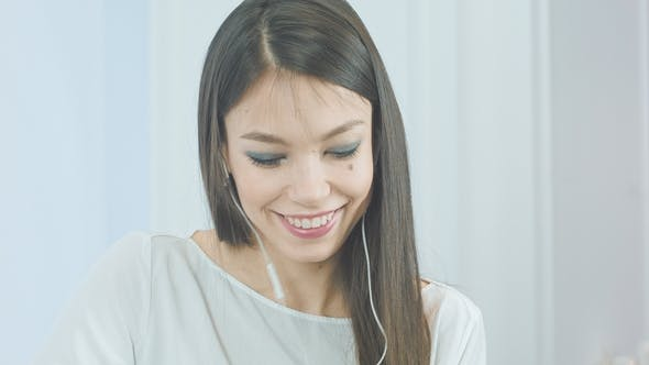 Thumbnail for Happy Young Woman Inserting Earphones Into Her Ears and Enjoying Music