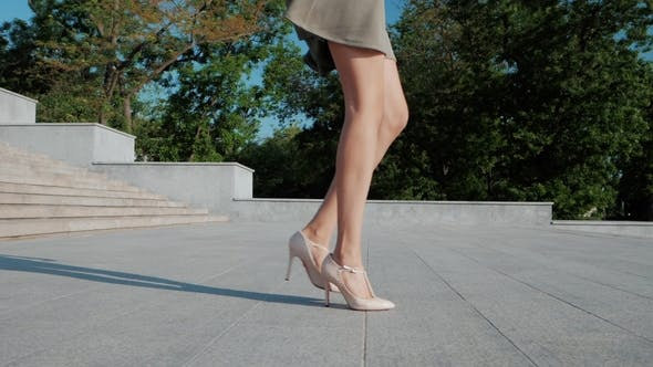Thumbnail for Legs with High Beige Heels Goes Down the Stairs of Big City