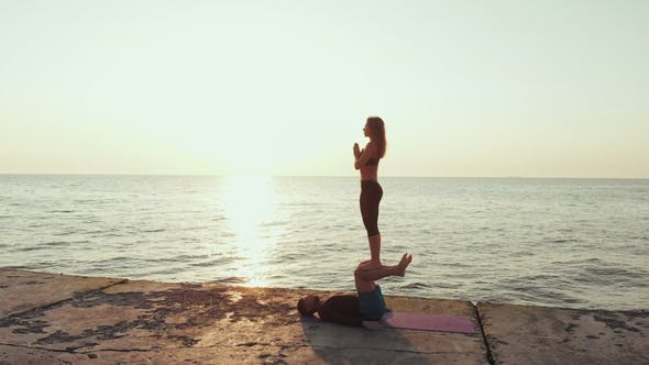 Thumbnail for Fit Young Couple Doing Acro-yoga at Sea Beach. Man Lying on Concrete Plates and Balancing Woman on
